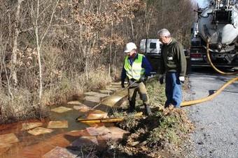 Dous operarios usan unha mangueira para succionar auga contaminada dunha charca dun humidal begontino. (Foto: N. Rodríguez)